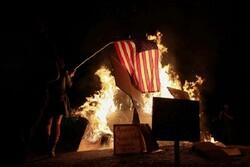متظاهرون امريكيون يحرقون العلم الامريكي في مدينة بورتلاند