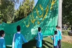 پرچم مزین به نام امام علی(ع) در میدان پژوهش همدان به اهتزاز درآمد