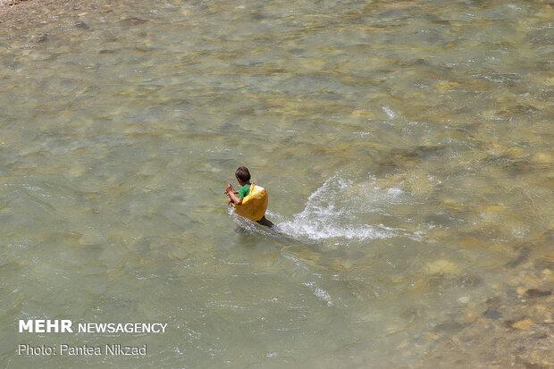 یکی از کودکان قسمت کم عمق تر رود را برای عبور از آن انتخاب کرده است. این تصاویر مربوط به تابستان است که حجم آب رودخانه کاهش پیدا می کند.