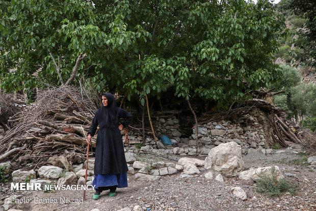 یکی از اهالی روستا در کنار خانه خود ایستاده است.
