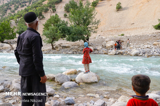تعدادی از اهالی در حال صحبت کردن با یکدیگر در دو سوی رود می باشند.
