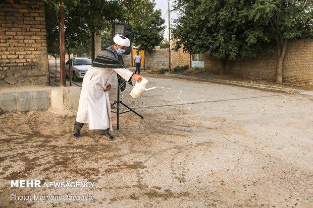 روحانی در حال آب پاشی محل روضه