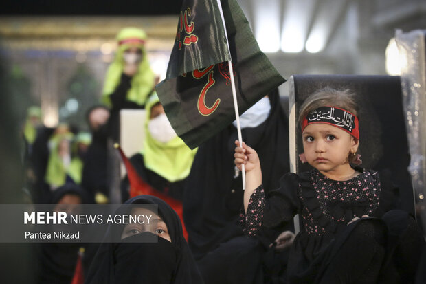 کودک سه ساله ای  که به یاد سه ساله کربلا، حضرت رقیه (ع) در حرم امام (ره) پرچم هایی با نام سیدالشهدا در دست دارد