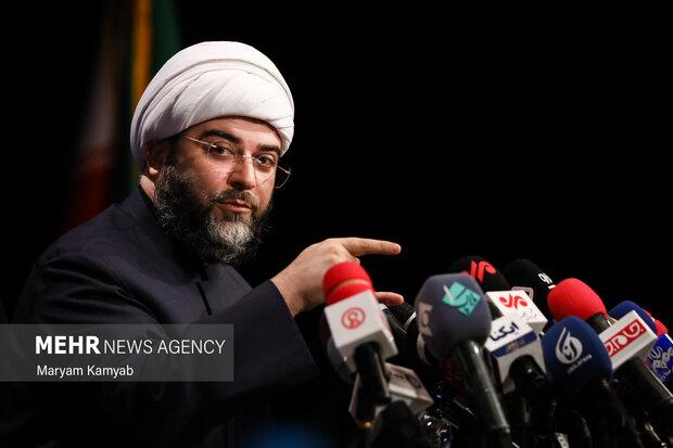 حجت الاسلام محمد قمی رئیس سازمان تبلیغات اسلامی در حال گفتگو با خبرنگاران حاظر در نشست خبری  است
