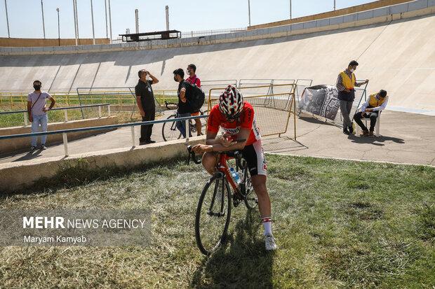 یکی از شرکت کنندگان رقابت های دوچرخه سواری پیست قهرمانی کشور در حال استراحت است .