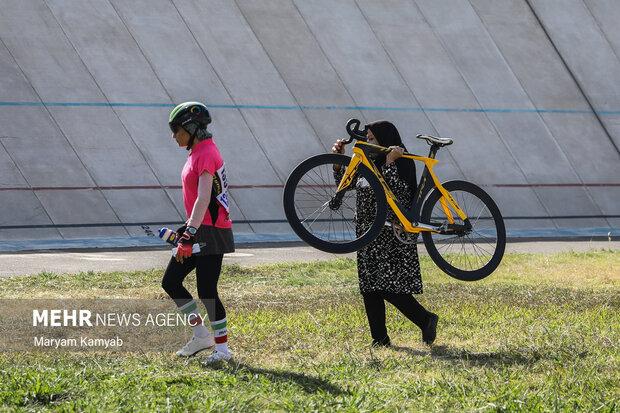 همراه یکی از شرکت کنندگان در حال حمل دوچرخه وی است