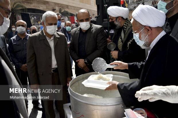 حمیدرضا ارباب سلیمانی مشاور وزیر فرهنگ در امور فرهنگی و دینی در حال کشیدن غذای نذری است