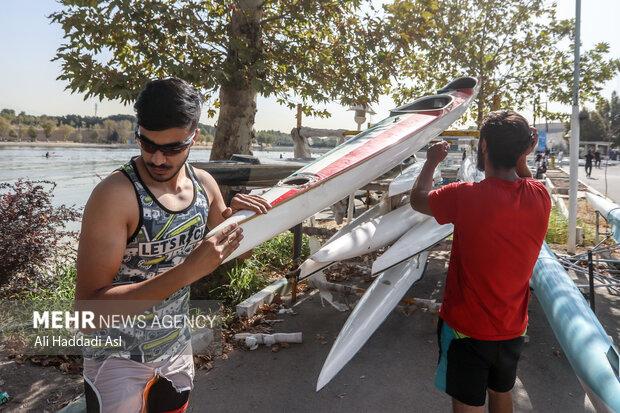 قایقران های هر تیم پیش از مسابقه قایق خود را برای وزن کشی آماده می کنند