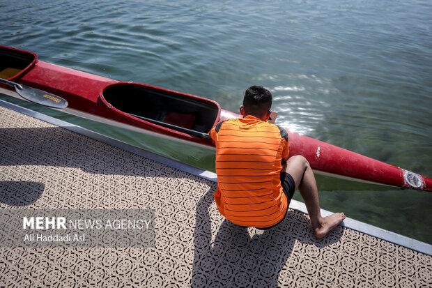 قایقرانی برای انجام مسابقه در حال انداختن قایق خود در آب است