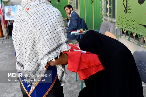 یکی از خانواده های دانش آموزان در حال بوسیدن پر چم گنبد امام حسین (ع) در یادواره شهدای دانش آموز هنرستان شهید مدرس است