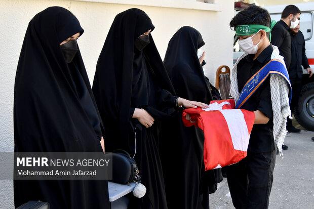 خانواده  دانش آموزان در حال تبرک از پرچم اما حسین (ع) در یادواره شهدای دانش آموز هنرستان شهید مدرس هستند