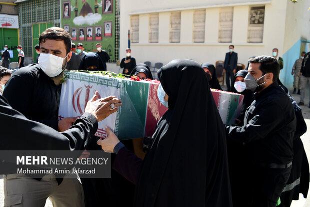 تابوت یک شهید گمنام هشت سال دفاع مقدس توسط خانواده های دانش اموزان در یادواره شهدای دانش آموز هنرستان شهید مدرس حمل می شود