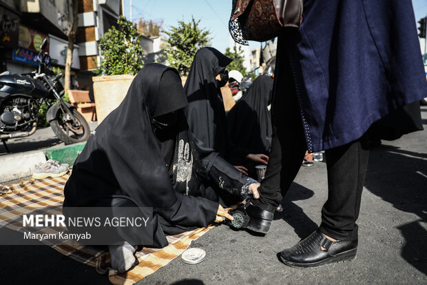 زنان در حال واکس زدن کفش زنان شرکت کننده در مراسم راهپیمایی اربعین حسینی در تهران هستند
