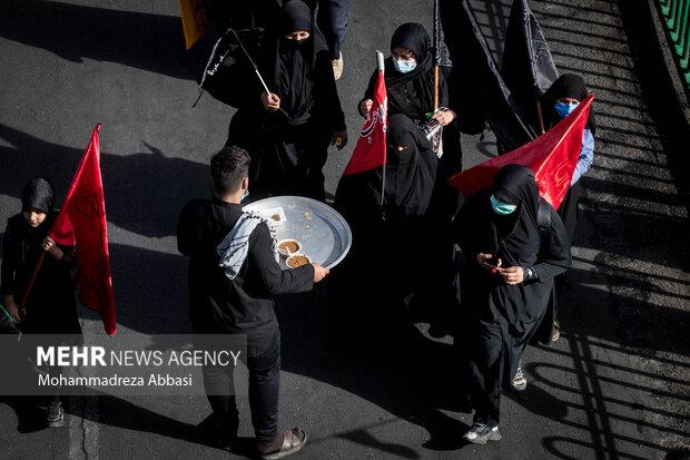 یکی از خادمان حسینی (ع) در حال پذیرایی از مردم تهران که در راهپیمایی جاماندگان اربعین حسینی حضور دارند ،  است