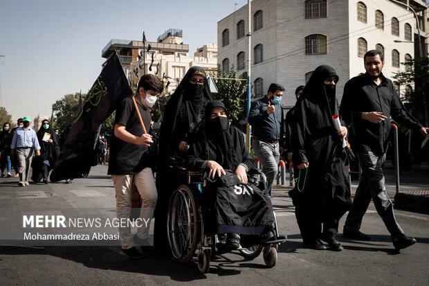 یکی از مردم تهران با مادر خود که بر روی ویلچر نشسته است  در مسیر پیاده روی جاماندگان اربعین حسینی (ع)  حضور دارد