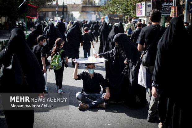 یکی از خادمان حسینی (ع) در حال پذیرایی از مردم تهران که در راهپیمایی جاماندگان اربعین حسینی (ع) حضور دارند ،  است