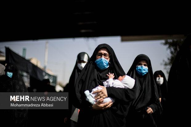 یکی از مردم تهران به همراه کودک خود در مراسم راهپیمایی جاماندگان اربعین حسینی (ع) حضور دارد