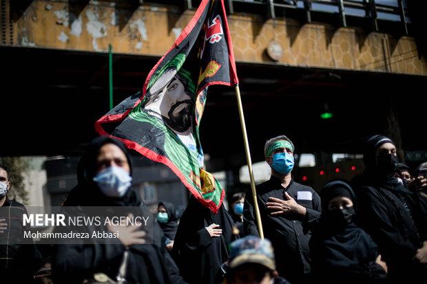 یکی از مردم تهران در مسیر پیاده روی جاماندگان اربعین حسینی (ع) پرچمی را که تمثال مبارک امام حسین (ع) بر روی آن نقش بسته است حمل میکند
