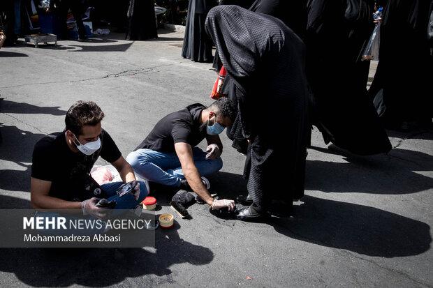 خادمان حسینی  در حال واکس زدن کفش زنان شرکت کننده در مراسم راهپیمایی اربعین حسینی در تهران هستند