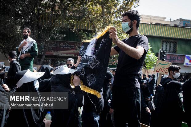 مردم در حال بوسیدن پرچم گنبد حضرت رقیه (س ) در طول مسیر پیاده روی جاماندگان اربعین حسینی (ع) هستند