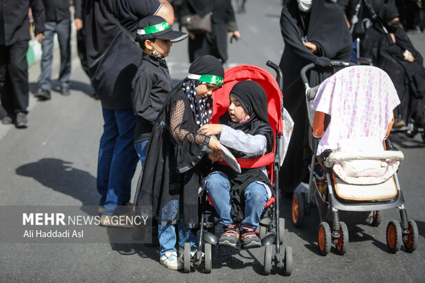 دو کودک در مراسم راهپیمایی جاماندگان اربعین حسینی(ع) حضور دارند