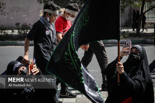 دو دختر جوان در حال عکاسی از پرچمی در مراسم راهپیمایی جاماندگان اربعین حسینی(ع)  هستند