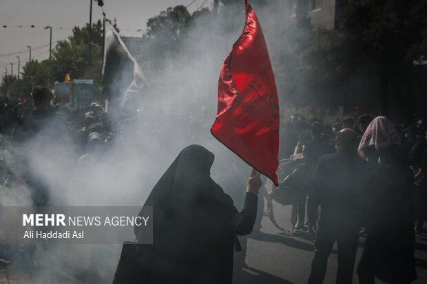 زنی با پرچم در مراسم راهپیمایی جاماندگان اربعین حسینی(ع) حضور دارد