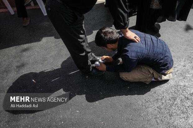 جوانی در حال تمیز کردن شرکت کننده ای در مراسم راهپیمایی جاماندگان اربعین حسینی(ع) است