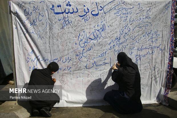 شرکت کنندگان در مراسم پیاده روی اربعین برای امام حسین دل نوشته های خود را ثبت می کنند
