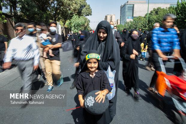 یک مادر در حال بستن سربند به فرزند خود در مراسم راهپیمایی جاماندگان اربعین حسینی (ع) است