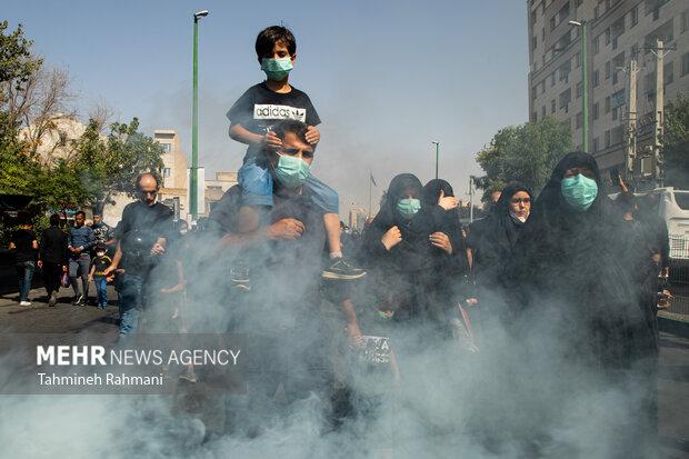 یک پدر به همراه فرزند خود در  مراسم راهپیمایی جاماندگان اربعین حسینی (ع) شرکت کرده است