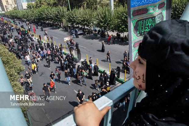 یک کودک در حال تماشای راهپیمایی جاماندگان اربعین حسینی (ع) است