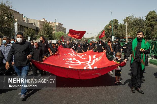 مردم تهران پرچم های عزاداری را در مسیر راهپیمایی جا ماندگان اربعین حسینی (ع) حمل میکنند