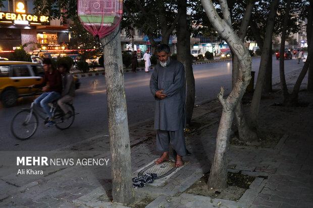 يك مرد افغان در حال خواندن نماز در يكى از خيابان هاى كابل است