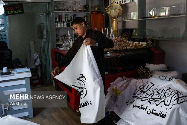 يك فروشنده در حال بسته بندى پرچم هاى طالبان است