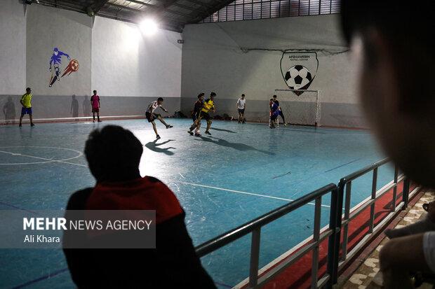 جوانان افغان در حال فوتبال بازى كردن در يكى از سالن هاى ورزشى در پل سرخ كابل هستند