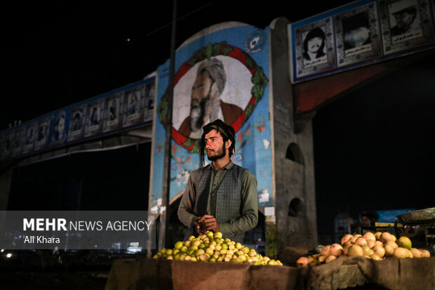 يكى دستفروش افغان در بازار سراى غزنى كابل در حال فروش میوه است