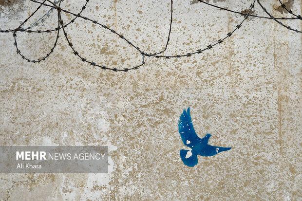 نمايى از يك طرح گرافيتى بر ديوار يكى از خيابان هاى كابل که نماد صلح است