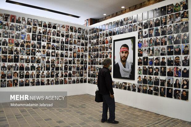 یک نفر از بازدید کنندگان در حال مشاهده تصاویر نمایشگاه است
