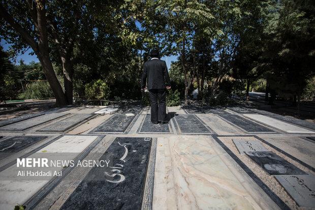 مردی با شمائل و پوششی قدیمی در حاشیه مراسم تشییع و خاکسپاری فتحعلی اویسی در قطعه هنرمندان بهشت زهرا در حال خواندن فاتحه برای اهل قبور است
