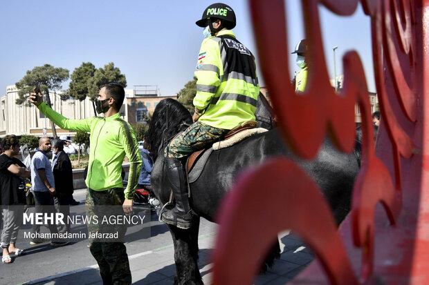 یک مرد در حال گرفتن عکس با اسب سواران یگان ویژه است .